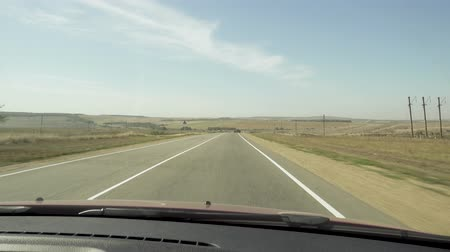 Driving on an asphalt road among hills and fields. view from the car through the windshield Stok Video