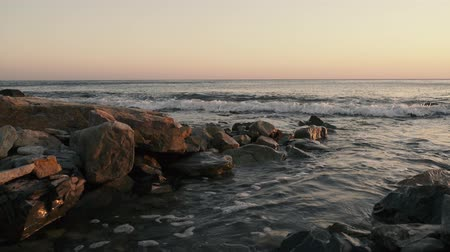 The evening lonely wave rolls over the stony shore and the camera turns left and right Stok Video