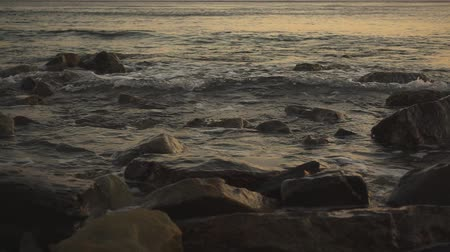 A beautiful evening sea and waves on a water surface roll on a stony shore slow motion