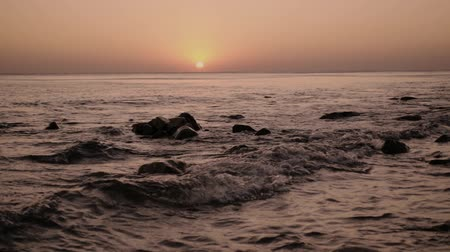 Slow mo a lonely wave on the setting sun rolls on a stony shore in the evening Stok Video