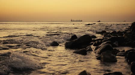 Ships in the sea in the roadstead and fishermen in a boat at sunset with a wave rolling on the shore slow mo