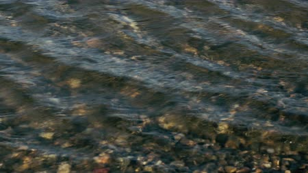 Small waves ripple on the water roll on the pebbles transparent water