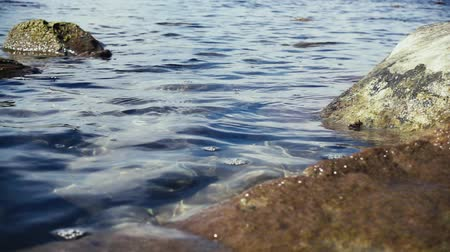 Slow mo small bubbles on the water surface of transparent blue water among large stones