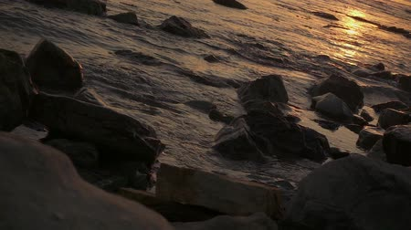 Slow motion small waves on the sea among the stones at sunset with the camera tilted to the right