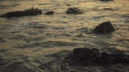 Excitement and splash of small waves about the rocks in the water on the beach at sunset and the background is out of focus slow motion. Stok Video