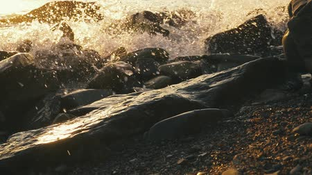 A lot of splash and splashes from a sea wave on a rocky beach at sunset slow mo