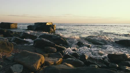 Slow motion two huge square stones in the water on a stony shore and rolling the wave in the setting sun Stok Video
