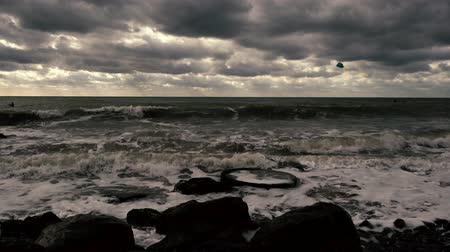 Two windsurfing in a disturbing sea, gray sky with clouds and waves on a stony shore