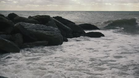 On the breakwater of large stones in the sea rolling wave slow motion
