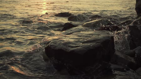 Splashes of water from a rolling wave on a stony shore in the setting sun slow mo Stok Video