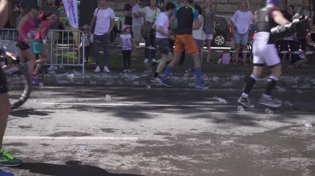 VIENNA, AUSTRIA, MAY 06 2018, WINGS FOR LIFE WORLD RUN MARATHON: Plastic cups for water under the feet of marathon runners Stok Video