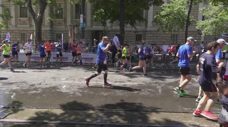 VIENNA, AUSTRIA, MAY 06 2018, WINGS FOR LIFE WORLD RUN MARATHON: Marathon runners slow down to drink water Stok Video