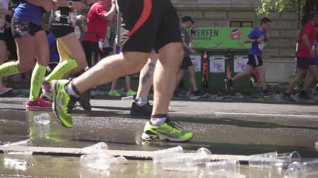 VIENNA, AUSTRIA, MAY 06 2018, WINGS FOR LIFE WORLD RUN MARATHON: Disposable cups and water under the feet of running marathon runners Slow Motion