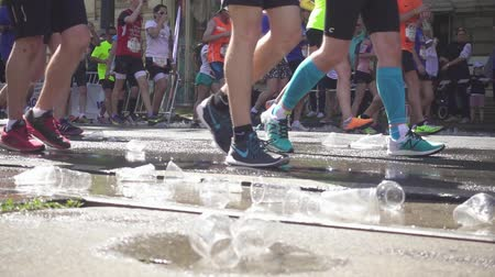 VIENNA, AUSTRIA, MAY 06 2018, WINGS FOR LIFE WORLD RUN MARATHON: Plastic cups and a puddle of water and legs of running marathon runners Slow Motion