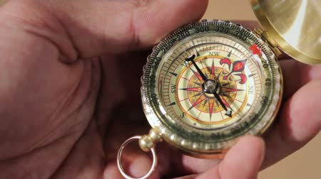 pusula : Hand holding a compass with swinging needle looking for North Stok Video