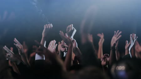 клуб : hands of crowds reaching up in the air during a night concert