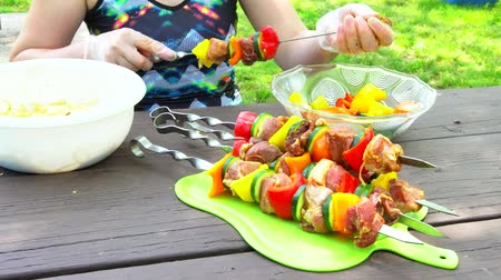 špejle : Assorted meat from pork and various on skewers vegetables for barbecue on cutting board, rotation