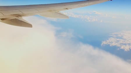stratosphere : Travel, Tourism, Destination Concept. Wing of an Airplane Flying Above the Clouds in Blue Sky. Stock Footage