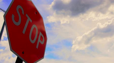 országúti : Stop sign with fast moving clouds Stock mozgókép