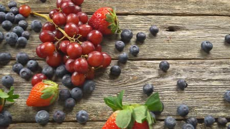 tápláló : Blueberries Grape Strawberries with wooden on wooden table SLOW MOTION hd video