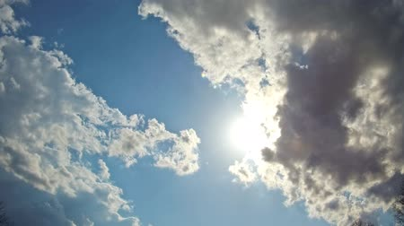 heaven : White clouds flying on blue sky with sun rays motion background