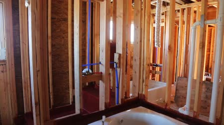 su tesisatı : New under construction bathroom interior with interior framing of new house under construction