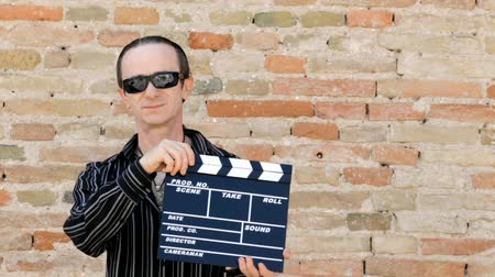актер : director with sunglasses in hand holds the Ciack Стоковые видеозаписи