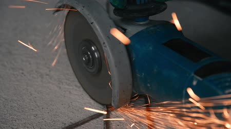 tokarka : Sparks from grinding metal by a blue grinding machine on a beton background loop