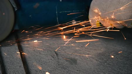 сварщик : Shiny sparks from grinding metal by a grinding machine loop on a gray beton background. Стоковые видеозаписи