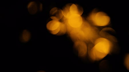 Blurry moving defocused gold lights on black background loop 무비클립