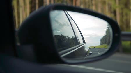 řídit : Shoot in rear-view mirror of car at road under evening sunset. Cinematic look loop footage.