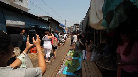 maeklong : Samut Songkhram - March 15 : Train passes through Maeklong Market Maeklong Railway Station, March 15, 2015 at Samut Songkhram, Thailand. Stock Footage