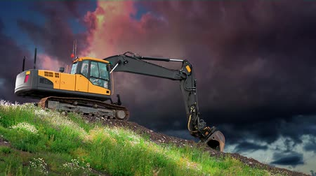 Digger on hill with grass and flowers with colorful sky Stok Video