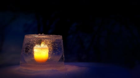 Ice lantern with candle in snow on cold evening Stok Video