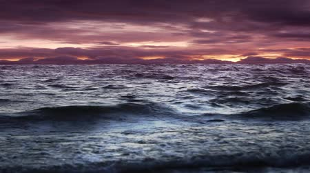 powerful waves in sea on stormy evening with purple and orange sky