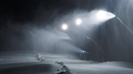 holiday makers : Snow machines in ski slope at night