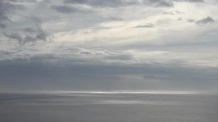 Time lapse with clouds moving over water surface of ocean