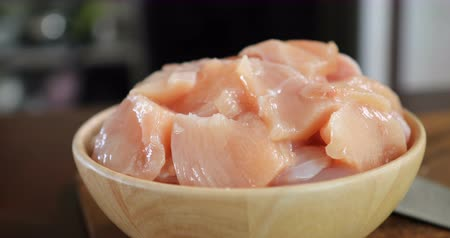 Close up the  cutting raw chicken meat in wooden bowl  in kitchen room , 4K Dci resolution Wideo