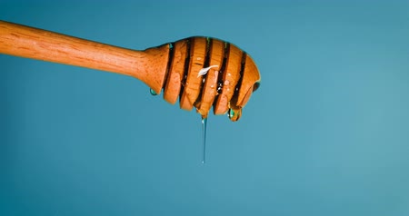 oil drop : Close up pouring golden sweet honey dripping  on honey dipper  vintage blue green  background , 4K Dci resolution