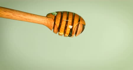 Close up pouring golden sweet honey dripping  on honey dipper  vintage blue green  background , 4K Dci resolution
