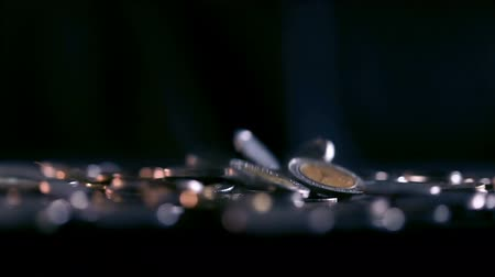малая глубина резкости : Close up money coin falling to the floor in dark light , business and financial for money saving or investment background concept with black copy space , extremely close up and shallow DOF