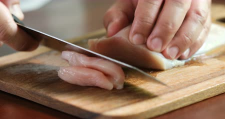 Close up the human hand cutting raw chicken meat on wooden chop board in kitchen room , 4K Dci resolution