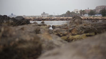 Wiew of Civitavecchia Italy beach filtered by blurred rocks