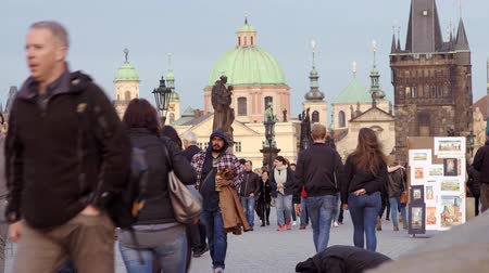 holiday makers : PRAGUE, CZECHIA - 9TH APRIL 2019: Tourists cross the Charles Bridge - Late evening - Early Sunset, April 2019