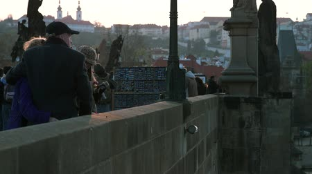 charles bridge : PRAGUE, CZECHIA - 12TH APRIL 2019: Tourists on the famous Charles Bridge during early Sunset during the Easter Holidays