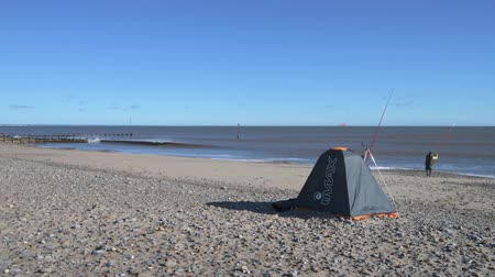 döküm : A lone fisherman walks and casts off to fish in the sea on Hornsea seafront Stok Video
