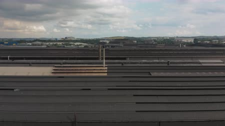 malom : SHEFFIELD, UK - 2ND AUGUST 2019: 4K Aerial pan along Forgemasters industrial steel mill roof with the sky in the background and Ikea and DSA arena.