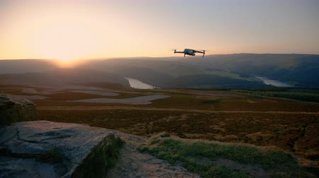 kural : DERBYSHIRE, UK 4TH AUGUST 2019: A DJI Mavic 2 Pro drone flies off into the distant sunset