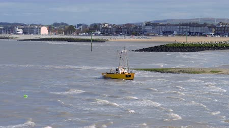torrente : An orange fishing boat anchored in Morecambe bay in stormy weather