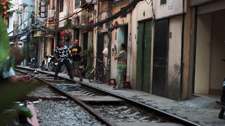 mozdony : Hanoi, Vietnam - 18th October 2019: Tourists pose for photos on the famous train street, now closed due to dangerous behaviour